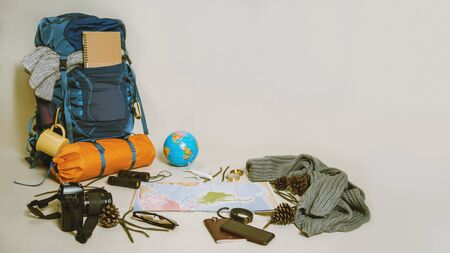 Tourist planning vacation with the help of world map with other travel accessories around. smartphone, film camera and sunglasses on a White background. Travel backpack 스톡 콘텐츠