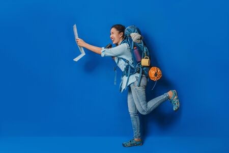 Side view of Woman traveler with suitcase backpack Blue color and equipment for travelers Vacation with a map, on Blue color background. Travel backpack