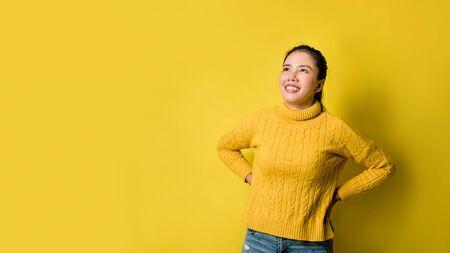 Portrait of happy young woman laughing against yellow wall. Photo of positive excited. person in sweater rejoices on yellow studio background.