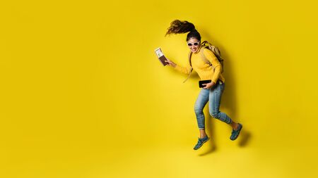 Woman traveler with suitcase, holding passport with ticket on Yellow background. Portrait of smiling happy girl in the yellow dress. people traveler 스톡 콘텐츠
