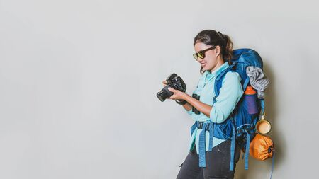 Concep image of a girl with a backpack in a handheld camera on a white background. travel backpack. Travel around the world.
