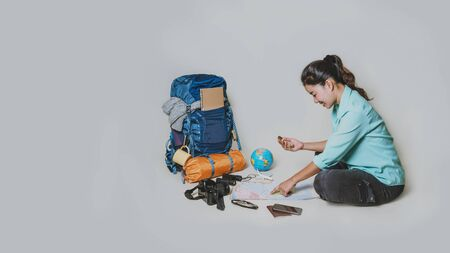 Tourist planning vacation with the help of world map with other travel accessories around. Woman traveler with suitcase on white background. Concept travel backpack 스톡 콘텐츠