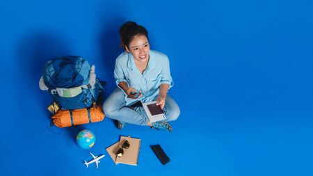 Tourist planning vacation with the help of world map with other travel accessories around. Woman traveler with suitcase on Blue color background. Concept travel backpack