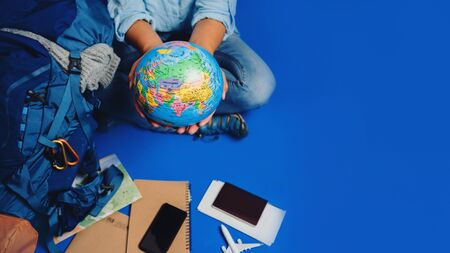 Tourist planning vacation with the help of world map with other travel accessories around. Woman traveler with suitcase on Blue color background. Girl with a ball globe in the hand. Travel backpack 스톡 콘텐츠