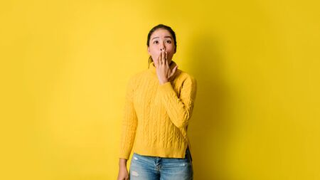 Photo of young woman positive excited on yellow studio background.