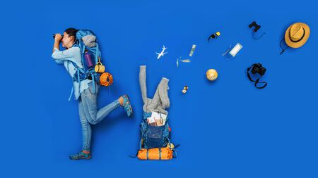 The concept of organizing equipment for traveling Put on the Luggage. Young asian traveler happy in Blue shirt with backpack with and equipment for travelers Vacation. Travel backpack.