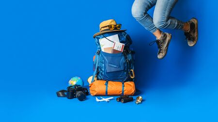 Tourist planning vacation with the help of world map with other travel accessories around. Woman traveler with suitcase on Blue color background. Concept travel backpack 스톡 콘텐츠