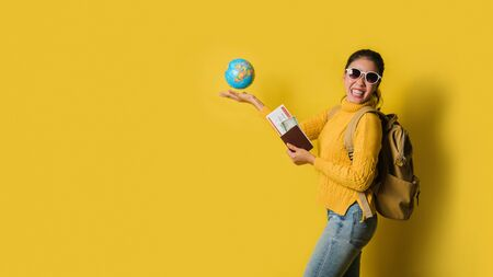 Woman traveler with suitcase, holding ball globe in the hand with passport and ticket on Yellow background. Portrait of smiling happy girl, concept of traveling around the world. Travel backpack