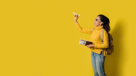 Woman traveler with suitcase, holding aircraft in the hand with passport and ticket on Yellow background. Concept of traveling around the world. Travel backpack 스톡 콘텐츠