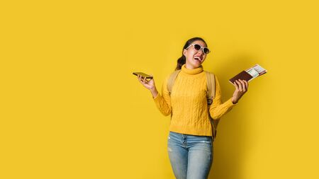 Woman traveler with suitcase, holding passport and ticket in the hand and mobile phones on yellow background. concept of traveling around the world. Travel backpack