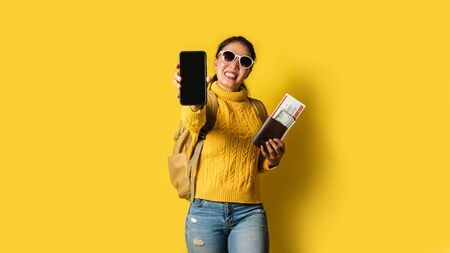 Woman traveler with suitcase, holding passport and ticket in the hand, and submit mobile phones coming in front of the camera on yellow background. Travel backpack