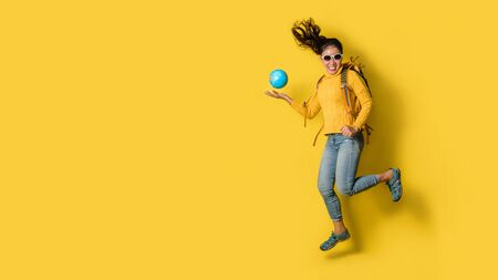 Woman traveler with suitcase, holding ball globe in the hand on Yellow background. Portrait of smiling happy girl with space copy the text. Travel backpack