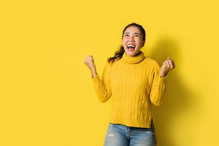 Portrait of a happy Asian woman screaming an excited and celebrating success isolated over yellow background. Succeed