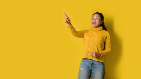 Portrait of an excited young blonde girl pointing with hand and finger to the side looking at the camera over yellow background. Pointed to the presentation. Space for text