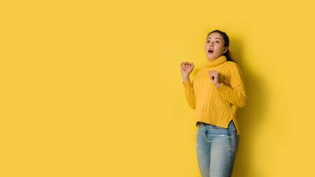 Portrait of a shocked young girl at copy space isolated over yellow background. 스톡 콘텐츠