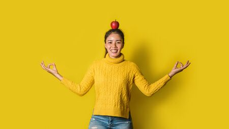 Cheerful young woman on yellow background in studio. A girl with an apple resting on her head while doing yoga. The concept of exercise for good health. Health lover