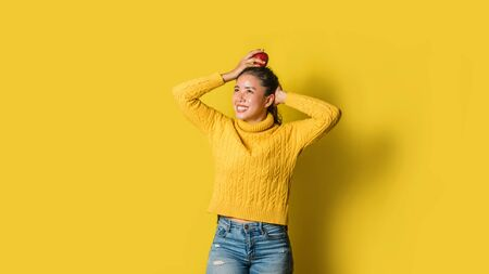 Cheerful young woman on yellow background in studio. A smiling and happy girl with an apple resting on her head. The concept of exercise for good health. Health lover