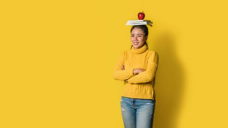 Cheerful young woman on yellow background in studio with a book and a red apple on her head. A smiling and happy girl. The concept of exercise for good health. Health lover