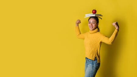 A girl with a book on her head and a red apple in her hand while doing yoga on yellow background. The concept of exercise for good health. Health lover