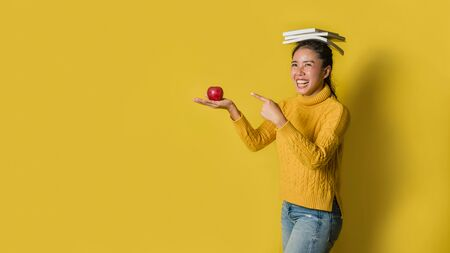 A girl with a book on her head and a red apple in her hand while the other hand points to the apple on yellow background. The concept of exercise for good health. Health lover