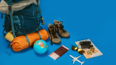The concept of organizing equipment for traveling Put on the Luggage. concept accessory for travelers Vacation with a map,  passport on Blue color background. Travel backpack