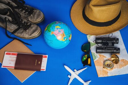 Tourist planning vacation with the help of world map with other travel accessories around. smartphone, film camera and sunglasses on a Blue background. Travel backpack 스톡 콘텐츠