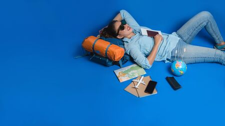 Tourist planning vacation with the help of world map with other travel accessories around. Woman traveler sleeping relax in hand holding a ticket with a passport on blue background. Travel backpack 스톡 콘텐츠