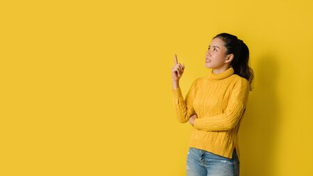 Portrait of an excited young blonde girl pointing with hand and finger to the side looking on yellow background. Pointed to the presentation. Space for text
