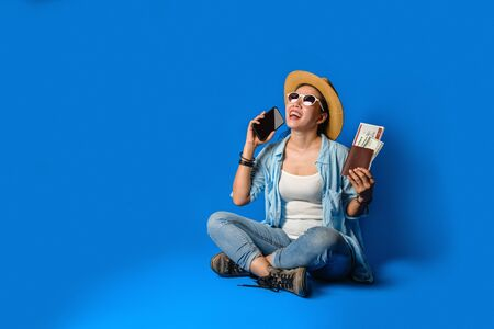 Traveler girl in a blue dress is smiling happy with a cheerful face and holding passport with holding mobile phones in the hand, on blue color background. concept travel 免版税图像