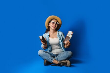 Traveler girl in a blue dress is smiling happy with a cheerful face and holding passport with holding mobile phones in the hand, on blue color background. concept travel Stok Fotoğraf