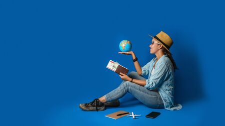 Young asian traveler happy in blue shirt holding passport with holding ball world in the hand. concept travel with equipment for travelers Vacation, on Blue color background. Travel relax