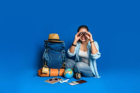 Young asian traveler happy woman in Blue shirt with backpack with and equipment for travelers Vacation with a map, on Blue color background. Travel backpack