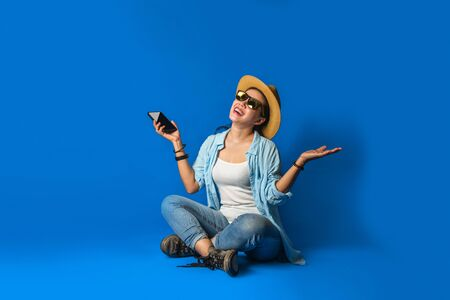A beautiful girl in a blue dress is smiling happy with a cheerful face  and holding mobile phones in the hand, on blue color background. Woman traveler