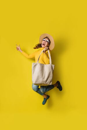 Portrait of an excited beautiful girl wearing dress and sunglasses holding shopping bags. Cheerful young woman with handbag on yellow background. Shopaholic shopping Fashion.