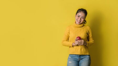 Cheerful young woman on yellow background in studio with a red apple in her hand. The concept of exercise for good health. Health lover
