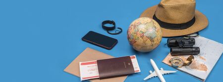 Tourist planning vacation with the help of world map with other travel accessories around. smartphone, film camera and sunglasses on a Blue background.