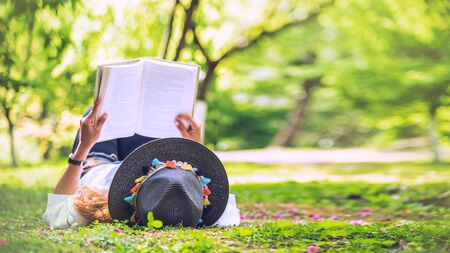 Freedom traveler woman Lying down reading in the The park and enjoying a beautiful nature. space for text.