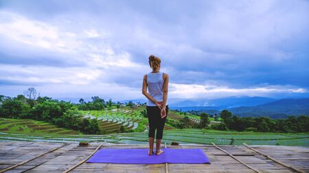 Freedom traveler woman relax in the holiday. Play if yoga Stand landscapes natural on the mountains and Field Rice. 免版税图像