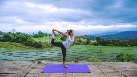 Freedom traveler woman relax in the holiday. Play if yoga Stand landscapes natural on the mountains and Field Rice. Stok Fotoğraf