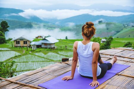 Asian woman relax in the holiday. Play if yoga. On the balcony landscape Natural Field Stok Fotoğraf