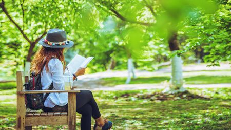 Freedom traveler woman sitting and reading in the The park and enjoying a beautiful nature. space for text. Stok Fotoğraf