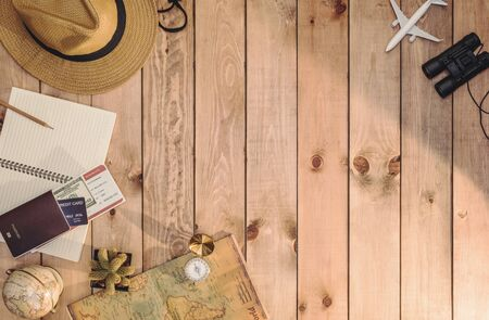 Overhead view of Traveler's accessories Essential vacation items, and Different objects on wooden background. Travel concept background