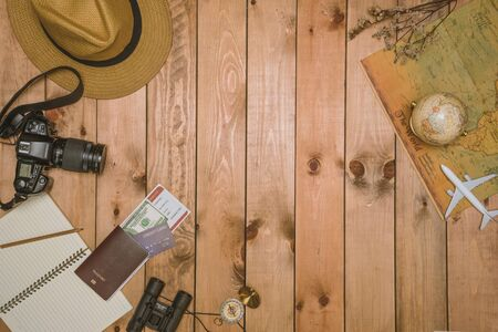 Overhead view of Traveler's accessories Essential vacation items, and Different objects on wooden background. Travel concept background, Prepare for travel