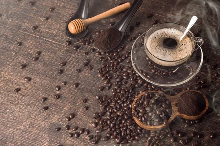 Coffee cup and Coffee beans spread on the table wooden old. Side view with copyspace for your text