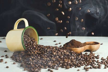 Coffee cup and beans spread and ground coffee in a wooden bowl on a white background Banco de Imagens