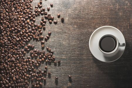 Cup of coffee with coffee beans on old table