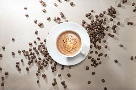 Cup of coffee cappuccino with coffee beans on a table vintage background Banco de Imagens
