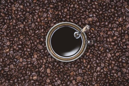 Cup of Black coffee placed, with Roasted Full frame coffee beans background