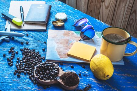 Travel concept using world map and compass along with other travel accessories. Coffee cup and Roasted coffee beans