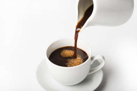 pouring a cup of coffee over white background Standard-Bild - 155035385
